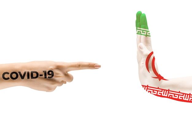이란과 코로나바이러스의 깃발로 색칠된 인간의 손 - 바이러스 확산의 개념. 악수는 위험하며, 전 세계적인 유행병입니다. 안전 유지. 예방, 안전, 전염병 확산 개념.