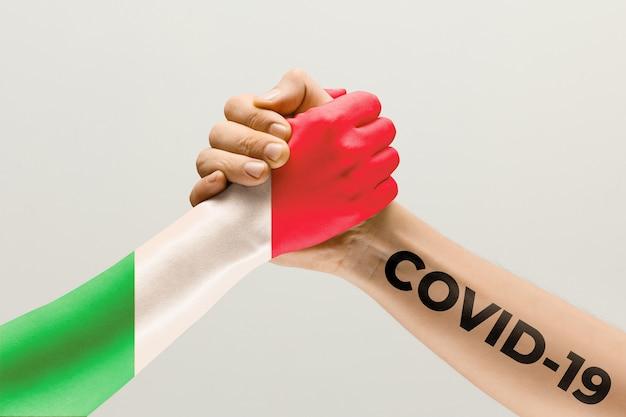 이탈리아와 코로나바이러스의 국기에 색칠된 인간의 손 - 바이러스 확산의 개념. 악수는 위험하며, 전 세계적인 유행병입니다. 안전 유지. 예방, 안전, 전염병 확산 개념.