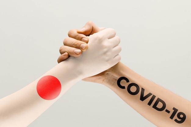 일본 국기와 코로나바이러스로 색칠된 인간의 손 - 바이러스 확산의 개념. 악수는 위험하며, 전 세계적인 유행병입니다. 안전 유지. 예방, 안전, 전염병 확산 개념.