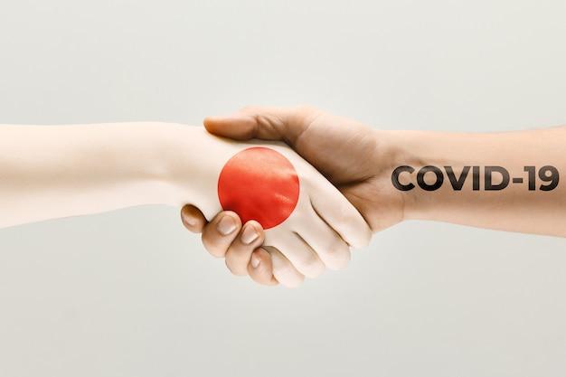 일본 국기에 색칠된 인간의 손과 바이러스 확산의 코로나바이러스 개념