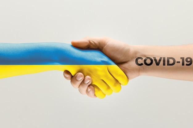 인간의 손은 우크라이나와 코로나바이러스의 깃발에 색칠되어 있습니다 - 바이러스 확산의 개념. 악수는 위험하며, 전 세계적인 유행병입니다. 안전 유지. 예방, 안전, 전염병 확산 개념.