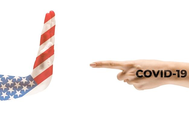 미국과 코로나바이러스의 국기에 색칠된 인간의 손 - 바이러스 확산의 개념. 악수는 위험하며, 전 세계적인 유행병입니다. 안전 유지. 예방, 안전, 전염병 확산 개념.