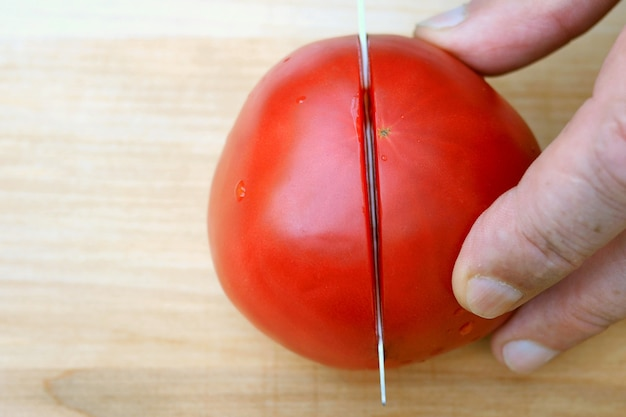 Human hands cut red pink tomato, with sharp kitchen knife, on wooden surface for cooking.