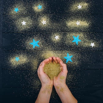 Human hands hold a shiny golden glitter in their palms and pour it at dawn on the table.