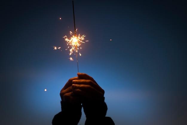 燃える火を持った人間の手が輝きます。新年、クリスマス、記念日を祝います。夜に燃える線香花火の花火を持っている手。休日のお祝いイベント