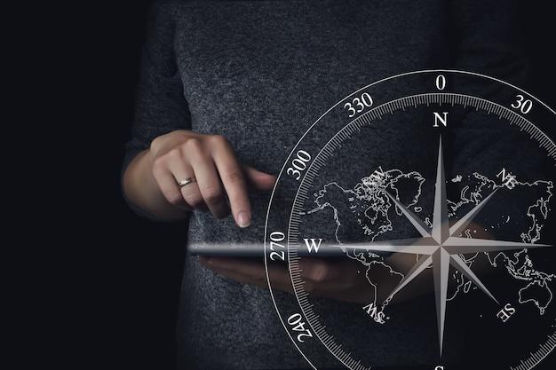 Человеческие руки, держа цифровой планшет с голограммой компас. концепция путешествия.