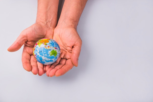 Human hands holding globe against white background