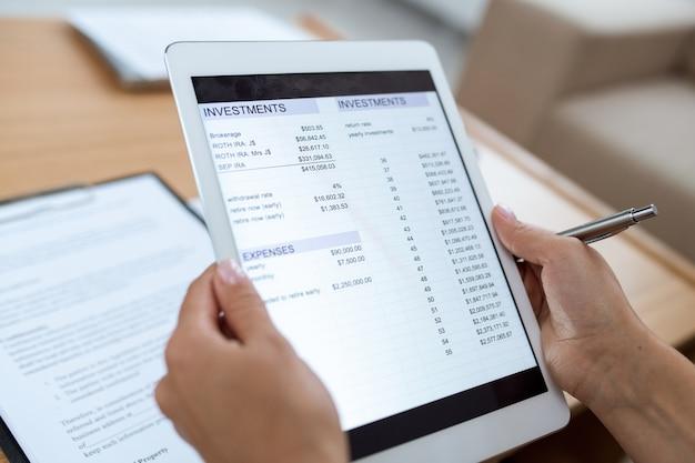 Человеческие руки держат тачпад с электронным документом, содержащим финансовую информацию