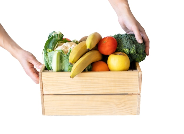 Human hands holding wooden box with different fruits and vegetables, isolated on white