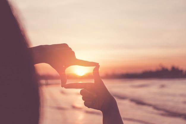 夕焼け空にフレームサインを作る人間の手。