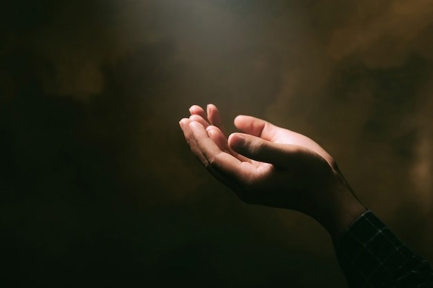 Human hands open palm up worship with faith in religion and belief in god on blessing background.christian religion concept background.