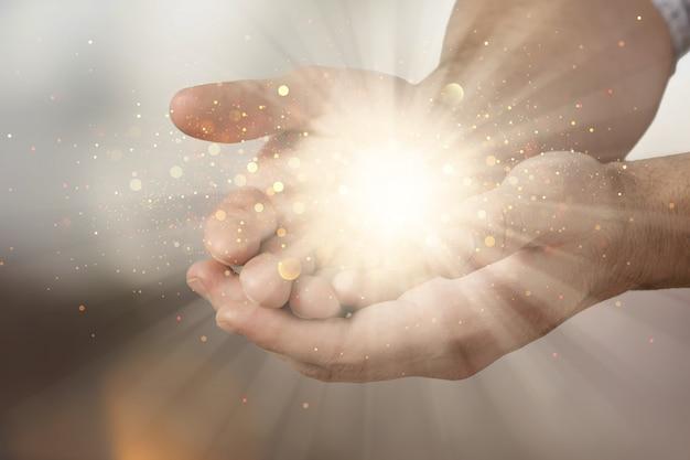 光が輝いて祝福を祈る人間の手