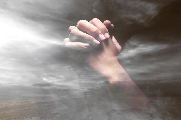 극적인 하늘 배경으로 신에게기도하면서 제기 된 인간의 손