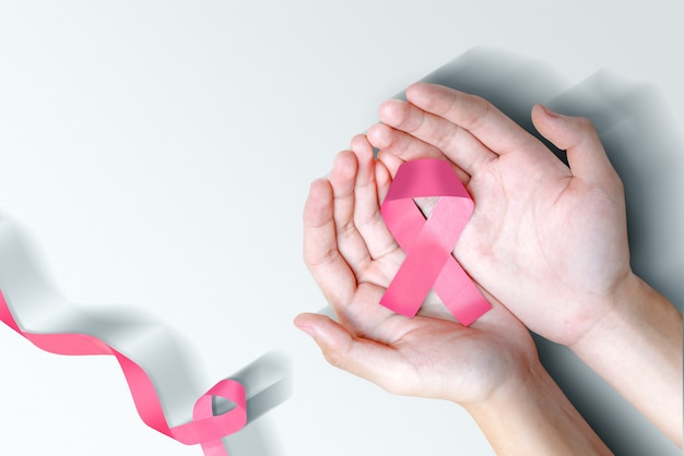 Human hands showing pink awareness ribbon