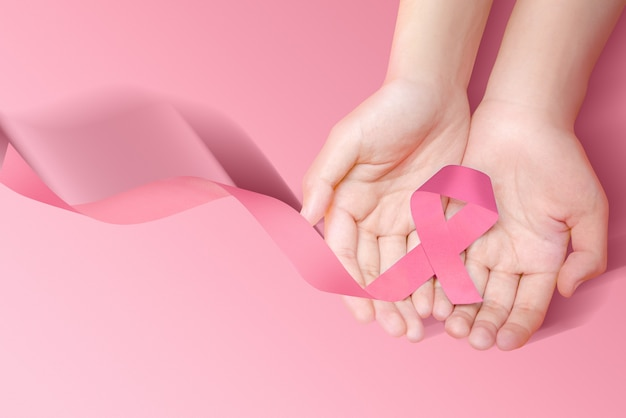 Human hands showing pink awareness ribbon