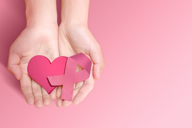 Human hands showing a pink heart and pink ribbon