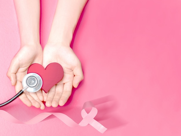 Human hands showing a pink heart and stethoscope with a pink ribbon