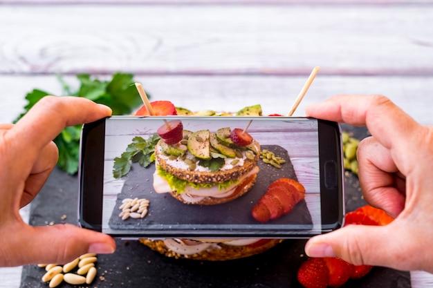 人間の手が、さまざまな野菜、七面鳥の肉、アボカドを種付きの全粒粉パンに入れた3層のサンドイッチに写真を撮ります。健康的な食事の概念。