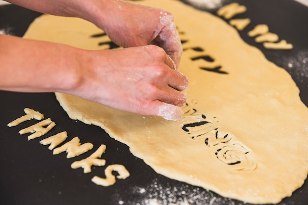Humanhands taking away dough letters