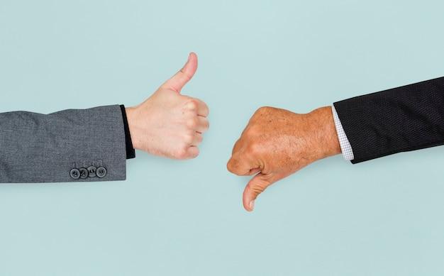 人間の手の親指アップ親指ダウンサインコンセプト
