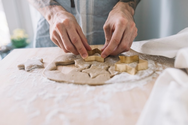 Human hands using cookie cutter on dough