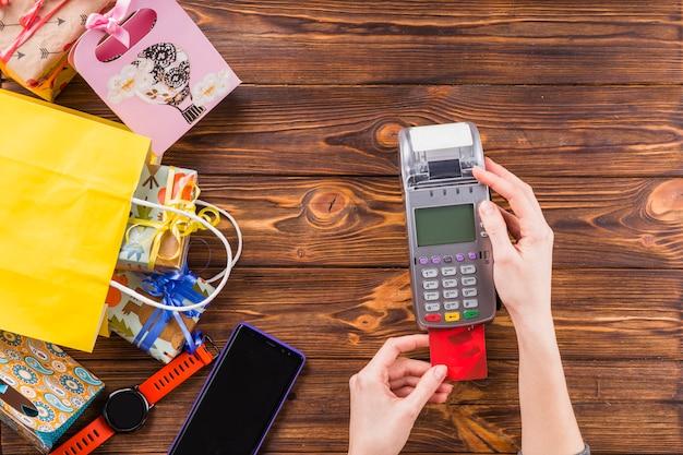 상점에서 지불을 위해 신용 카드 슬쩍 기계를 사용하는 인간의 손