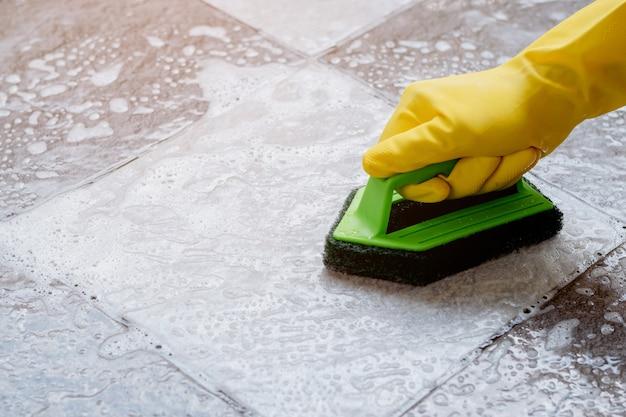 노란색 고무 장갑을 끼고 있는 인간의 손은 녹색 플라스틱 바닥 수세미를 사용하여 바닥 클리너로 타일 바닥을 문지르고 있습니다.