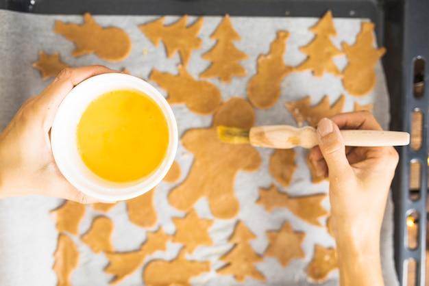 ビスケットの生地を塗って卵黄を持つ人間の手