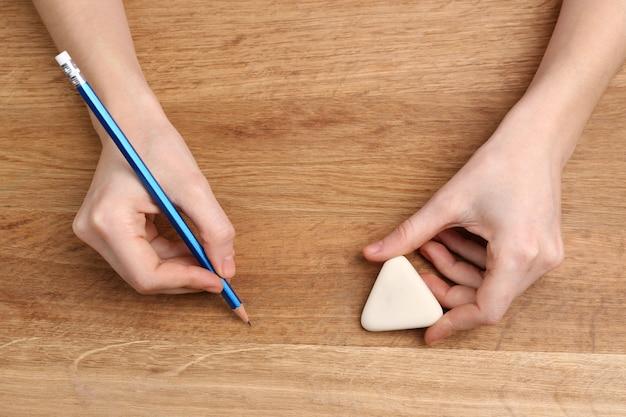 연필로 인간의 손과 나무 테이블에 고무 지우기