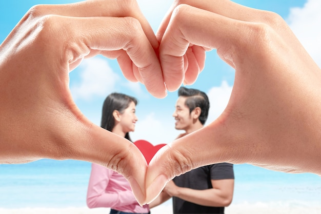 Human hands with the shape of the heart showing asian couples holding the red heart