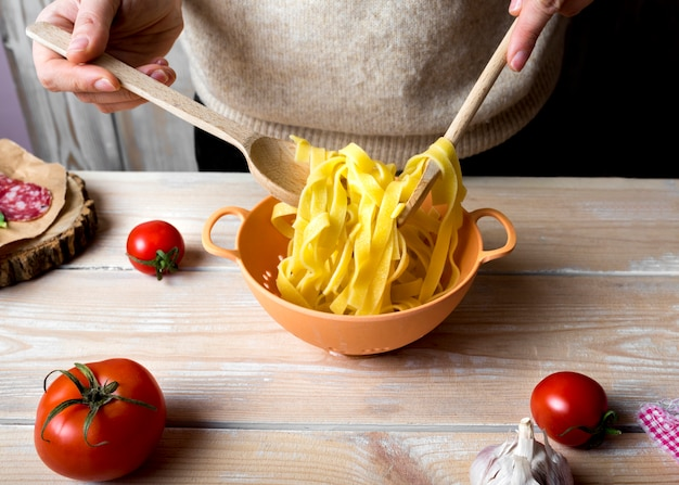 Human hands with wooden spoons mixing boiled spaghetti in colander over kitchen counter