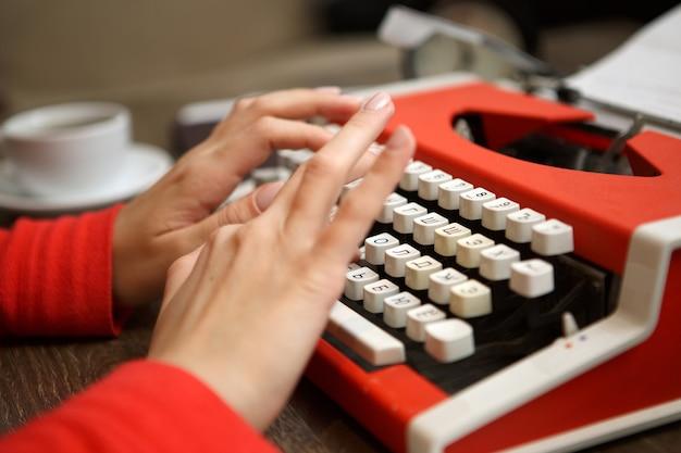 Человеческие руки пишут на красной пишущей машинке Premium Фотографии