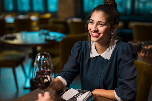 Human and happy woman clanging glasses of wine at table in cafe