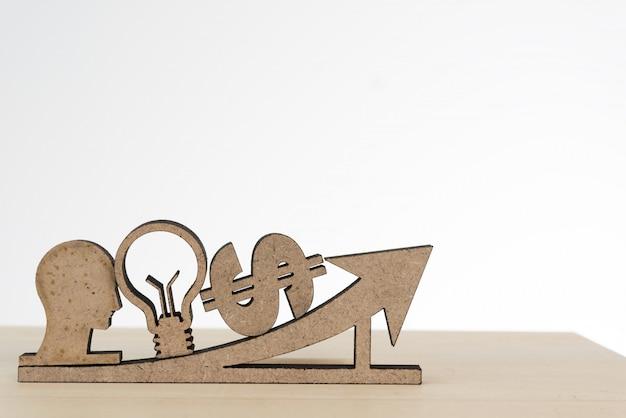 Человеческая голова, лампочка, знак доллара и знак стрелки на деревянном столе