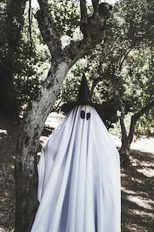 Человек в костюме призрак и волшебная шляпа возле дерева в лесу