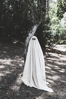 Человек в костюме призрака возле дерева в лесу