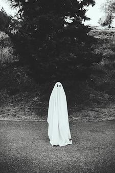 Человек в костюме призрак, стоящий на дороге