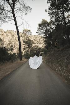 Человек в призрачном костюме с поднятыми руками идет по сельской дороге