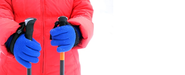 빨간색 스포츠 재킷과 파란색 장갑의 인간은 오른쪽에 텍스트를위한 여유 공간이있는 흰색 배경에 고립 된 겨울 시즌에 하이킹을위한 두 개의 막대기를 보유하고 photo