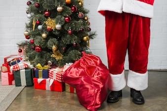 Human in Santa's suit near Christmas tree