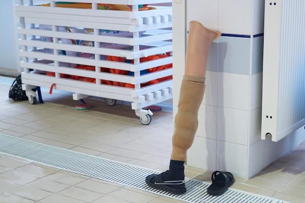 人間の脚の義足は、所有者が泳いでいる間、スリッパと一緒にプールの壁のそばに立っています
