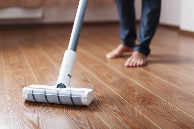 人間の足とコードレス掃除機の白いターボブラシが家の寄木細工の床を掃除します。洗浄のための最新技術。