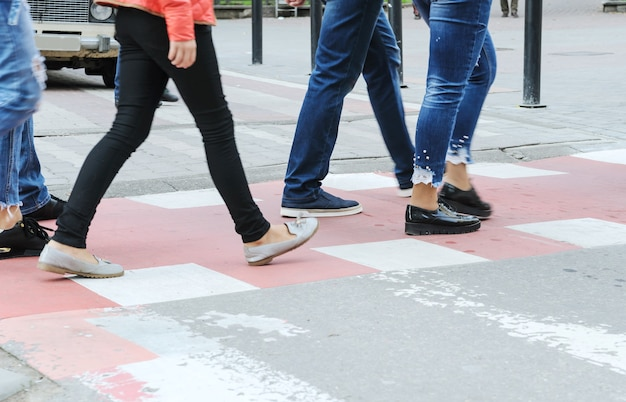Human legs are moving on a pedestrian crossing