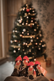 Human legs in funny socks near decorated fir tree