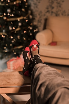 Human legs in funny socks near Christmas tree and settee
