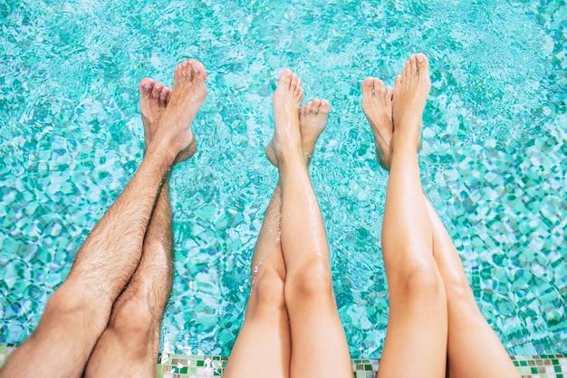プールの人間の足。サマーホテルでの休暇。水の背景に足。スイミングプールの家族
