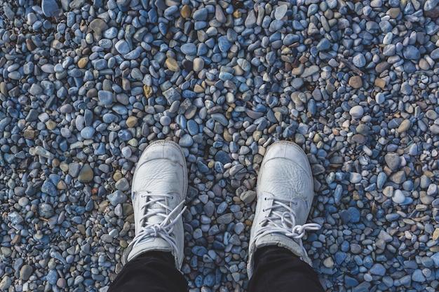 石のビーチに立っている白いスニーカーで人間の足