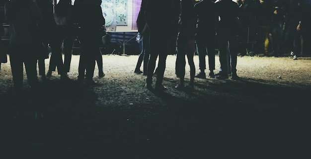 Human legs of people which waiting for music festival.