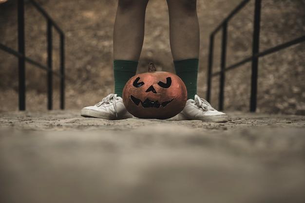 ハロウィンのカボチャと人間の足は公園の歩道に置か