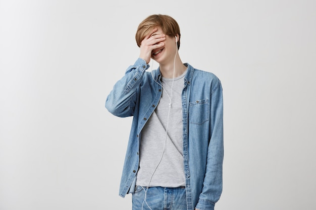 Human, leisure and modern technology concept. indoor shot of fair-haired young male in denim shirt, listens songs with headphones, doesn`t hear anything around, hiding his face behind his palm.